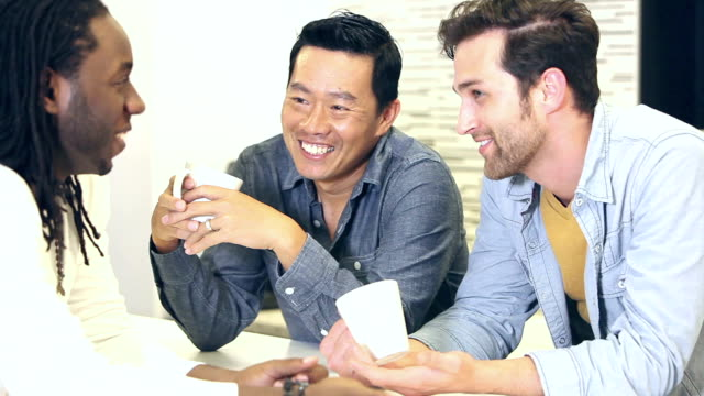 Multi-etnische mannen in kantoor praten, drinken koffie