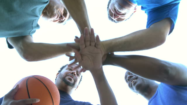 vídeos de stock e filmes b-roll de multi-ethnic men playing basketball, talking in huddle - domingo