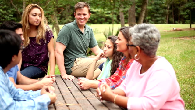 Multi-ethnic, mixed-age group of friends meeting together at park.