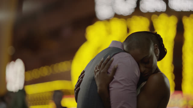 slo mo. multi-ethnic newlyweds embrace and rub noses on fremont st. in las vegas - millionnaire stock videos & royalty-free footage