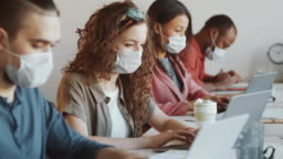 Multiethnic Office Workers in Protective Face Masks Using Laptops at Desk