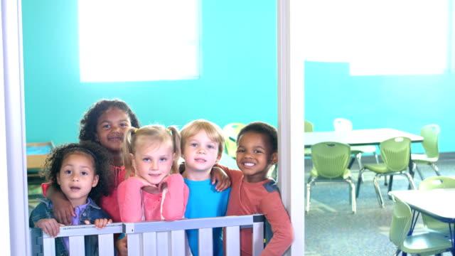multi-ethnic preschool children standing in doorway - arm around stock videos & royalty-free footage