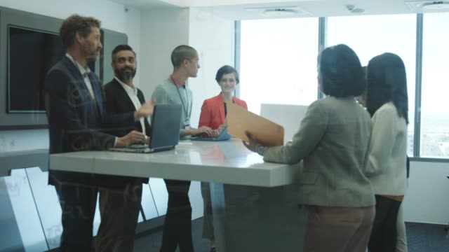 vidéos et rushes de multi-ethnic professionals planning in board room - être debout