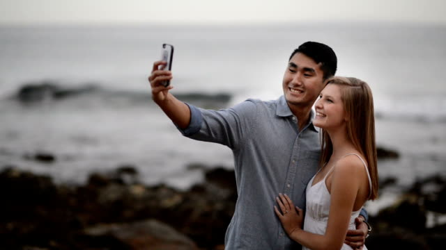 multi-ethnic romantic couple taking a selfie at the beach - honeymoon stock videos & royalty-free footage