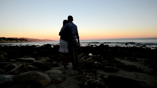 Multi-Ethnic Romantic Couple Watching the Sunset at the Beach