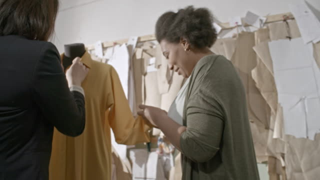 Multi-ethnic seamstresses chatting and adjusting dress on mannequin