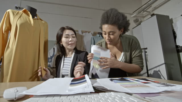stockvideo's en b-roll-footage met multi-ethnic seamstresses discussing design with client via video call - modeontwerper