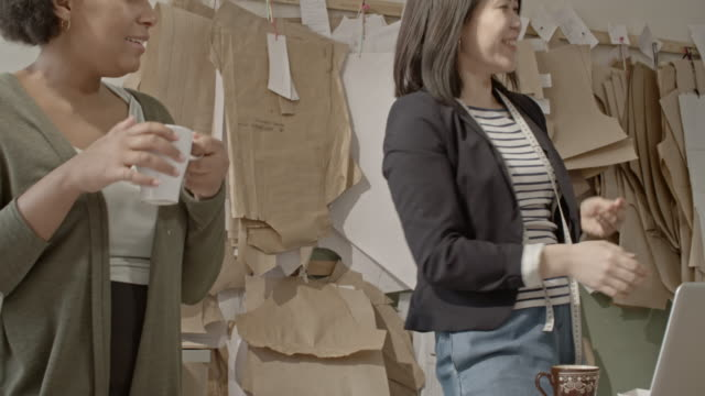 multi-ethnic seamstresses receiving food delivery in sewing workshop - パタンナー点の映像素材/bロール