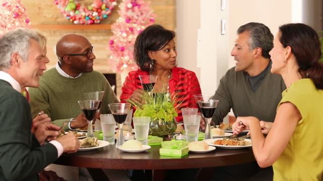 Multi-ethnic senior friends eating Christmas dinner.