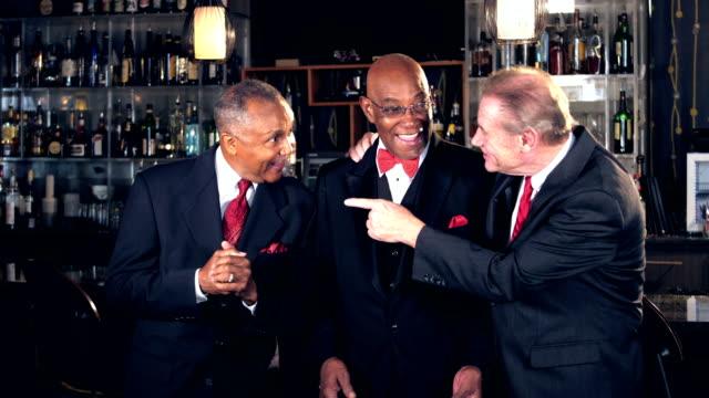 multi-ethnic senior men at bar wearing suits, talking - vita notturna video stock e b–roll