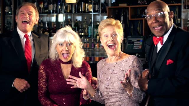 Multi-ethnic seniors at bar enjoying night out, surprise