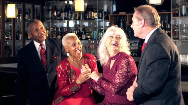 Multi-etnische senioren op bar genieten van avondje uit