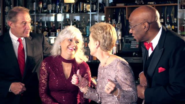 Multi-ethnic seniors at bar enjoying night out
