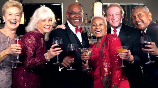 Multi-ethnic seniors at bar, toasting to camera