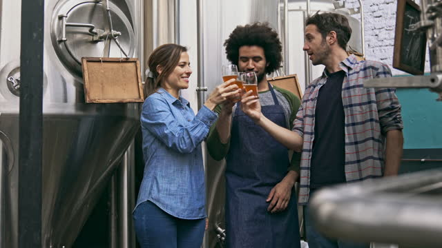multi-ethnic skilled craft brewers celebrating the success of the brewery company - mid adult stock videos & royalty-free footage