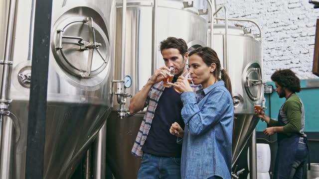 multi-ethnic skilled craft brewers sampling beer drawn from vat - tasting stock videos & royalty-free footage