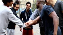 Multi-ethnic soccer team stacking hands on street