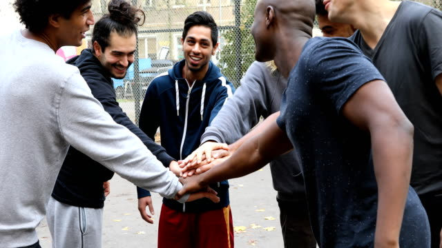multi-ethnic soccer team stacking hands on street - friendship stock videos & royalty-free footage
