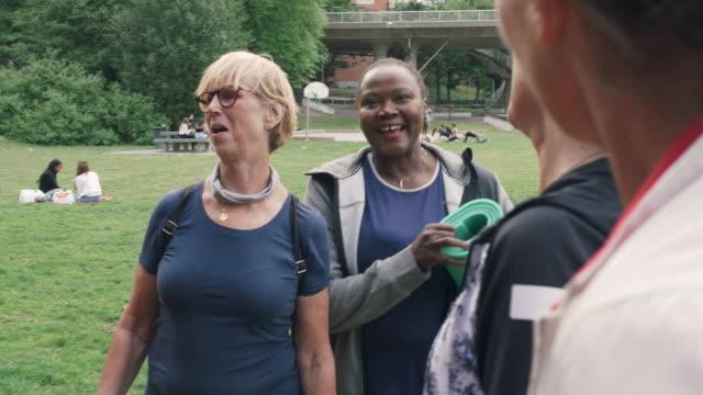 multi-ethnic sporty female friends talking in park - abbigliamento sportivo video stock e b–roll