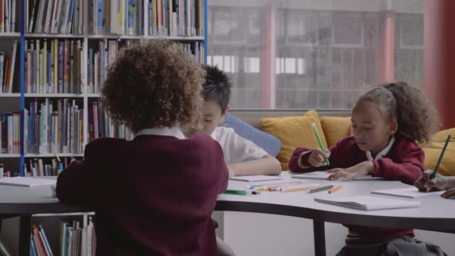 multi-ethnic students drawing in books at table - library stock videos & royalty-free footage
