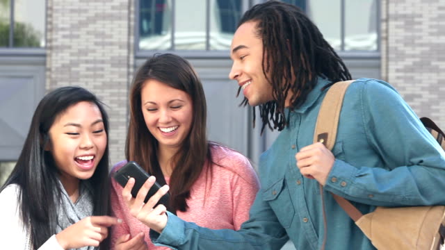 Multi-ethnic students looking and laughing at mobile phones