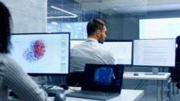 Multi-Ethnic Team of Computer Scientists Create Neural Network at Their Workstation. Office is Full of Displays Showing 3D Representations of Neural Networks.