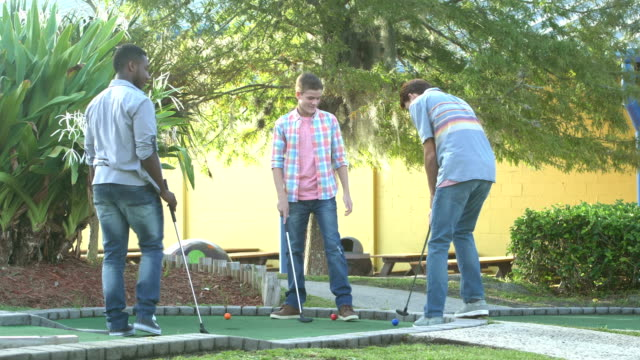 vídeos de stock e filmes b-roll de multi-ethnic teenage boys playing miniature golf - 12 13 years