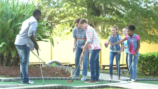 stockvideo's en b-roll-footage met multi-etnische tiener jongens spelen miniatuur golf - golf sport