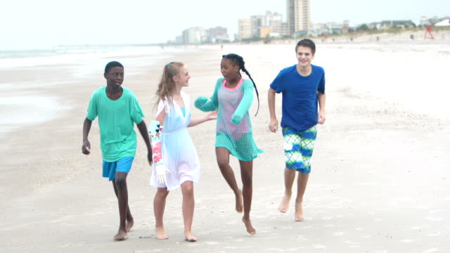 multi-ethnic teenage friends running on the beach - 12 13 years stock videos & royalty-free footage