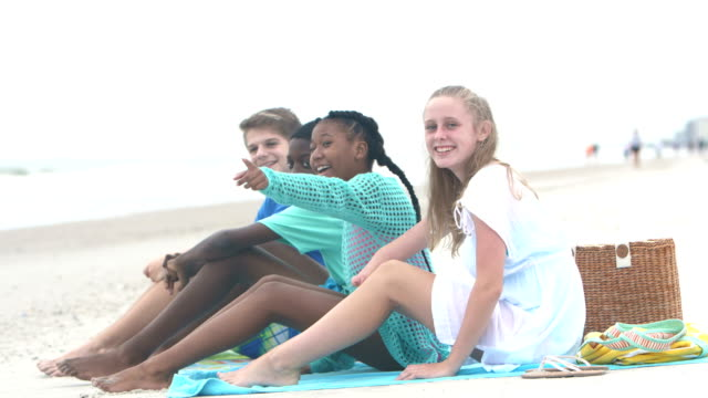 multi-ethnic teenage friends sitting on beach - 12 13 years stock videos & royalty-free footage