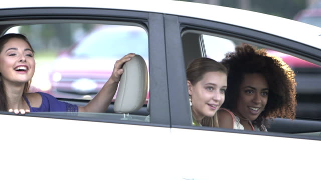 multi-ethnic teenage girls in a car, laughing, waving - learning to drive stock videos & royalty-free footage