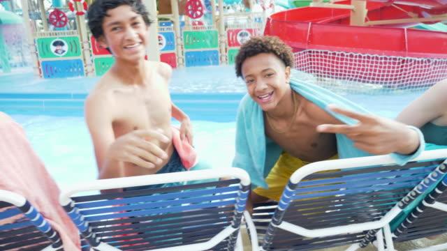 multiethnische jugendliche im wasserpark auf liegestühlen - multi ethnic group stock-videos und b-roll-filmmaterial