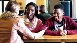 Multi-ethnic teenagers hanging out in coffee shop