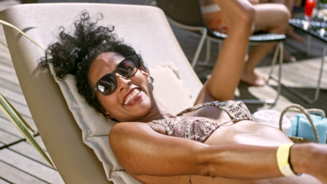 Multiethnic woman lying on the deckchair by the pool, dancing to the music and smiling into the camera on a sunny day