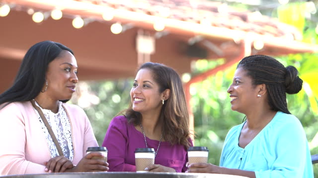 multi-ethnic women talking at outdoor table with coffee - minoranza video stock e b–roll