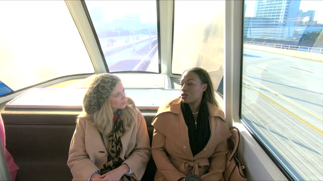 Multi-ethnic women talking, riding tramway to work