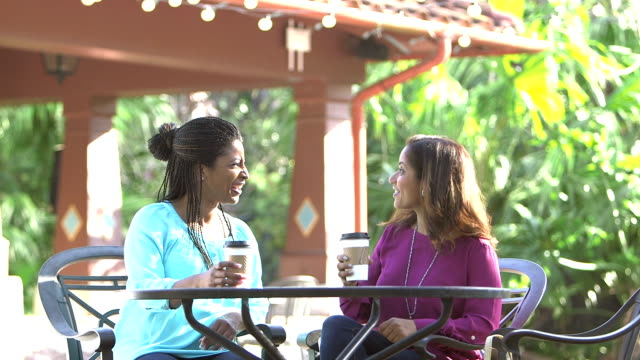 Multi-ethnic women talking, sit down at outdoor table