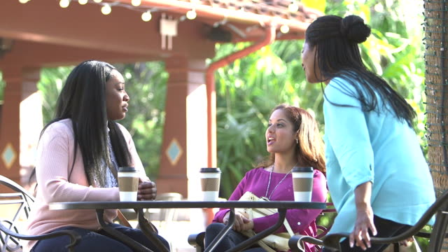 multi-ethnic women talking, sit down at outdoor table - simple living stock videos & royalty-free footage
