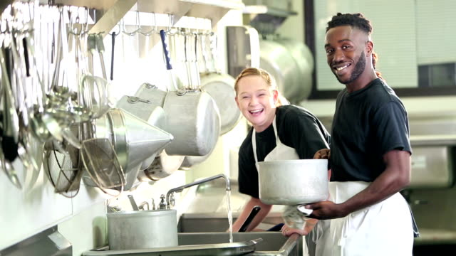 multi-ethnic workers in commercial kitchen washing pots - lavastoviglie video stock e b–roll