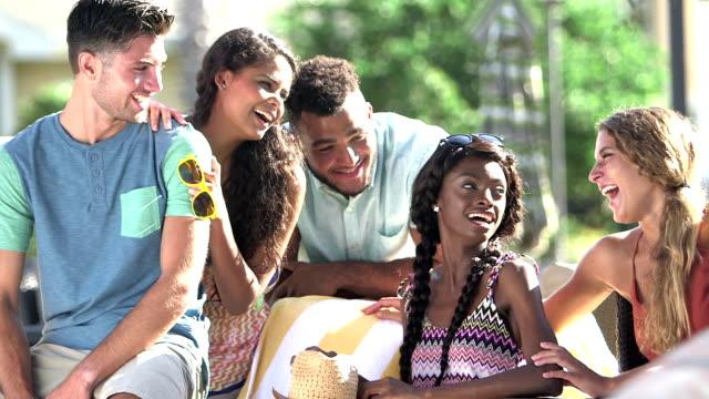 vidéos et rushes de multiethniques jeunes adultes suspendus sur patio - vie sociale
