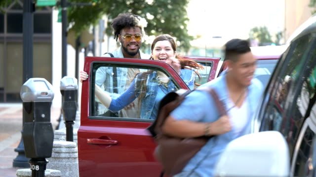 multi-ethnic young adults in city, getting in parked car - vehicle door stock videos & royalty-free footage