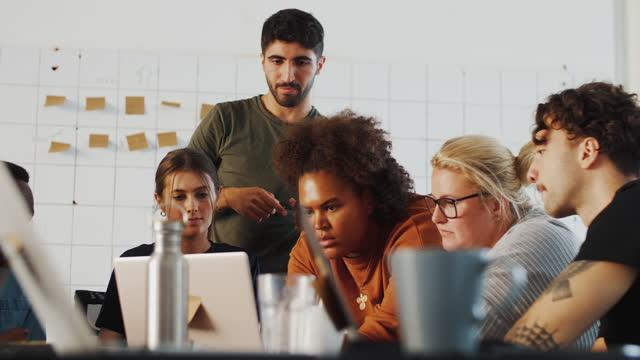 multi-ethnic young male and female computer programmers discussing over laptop at coworking space - medarbetarengagemang bildbanksvideor och videomaterial från bakom kulisserna