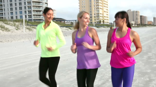 multi-ethnic young women power walking on beach - racewalking stock videos and b-roll footage