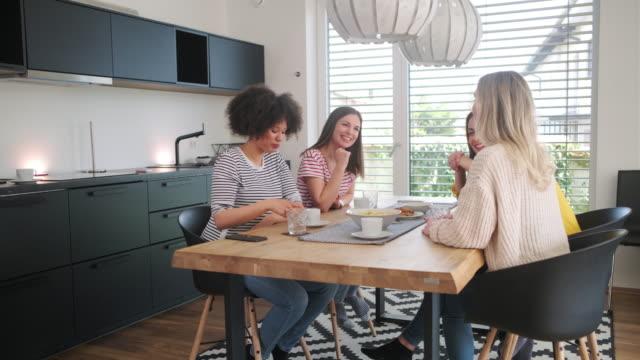 Multi-etnische jonge vrouwen praten op eettafel