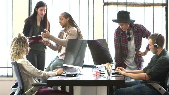 vidéos et rushes de multiethniques jeunes travailleurs dans les entreprises de démarrage, réunion - multi ethnic group
