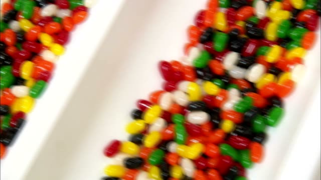 multi-flavored jelly beans fill compartments on a conveyor. - jellybean stock videos & royalty-free footage