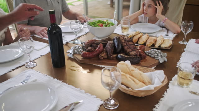 multi-generation argentine family beginning midday meal - cultura argentina video stock e b–roll