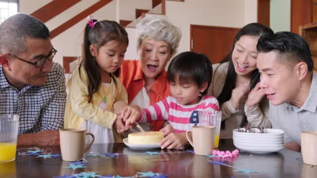 vídeos de stock, filmes e b-roll de família chinesa multi-geração que comemora o aniversário da criança em casa - família de várias gerações