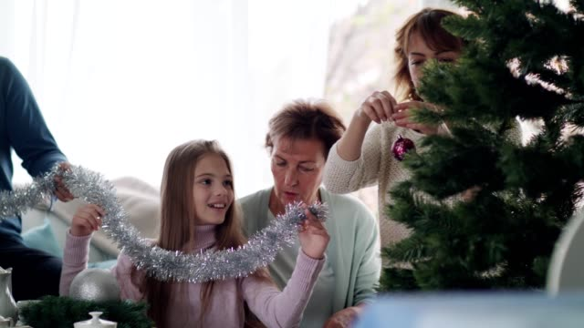 multi-generation family decorating the christmas tree - decorating the christmas tree stock videos & royalty-free footage