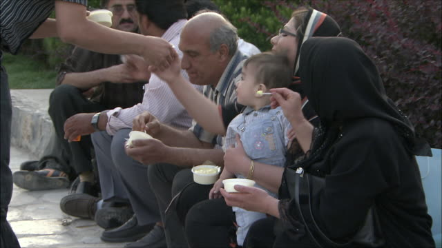 MS Multigeneration family eating ice cream in park, Isfahan, Iran